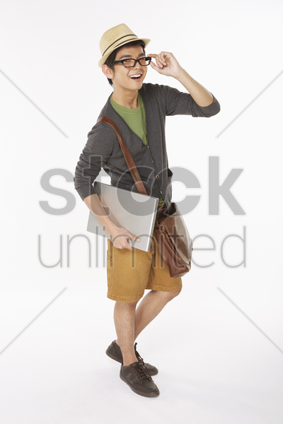 man holding on to a laptop, smiling stock photo