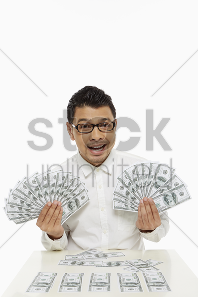 man holding piles of cash stock photo