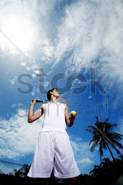 man holding tennis racquet and ball stock photo