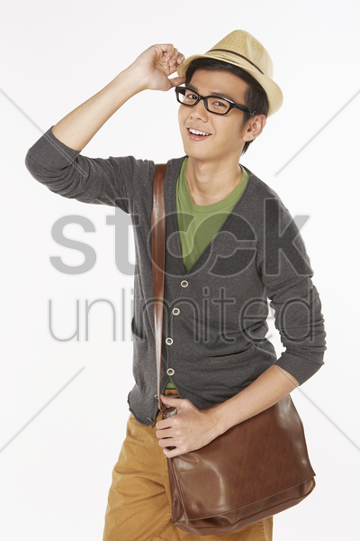 man holding the tip of his hat stock photo