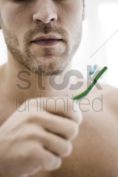 man holding toothbrush with toothpaste stock photo