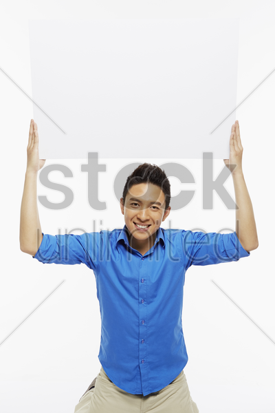 man holding up a blank placard stock photo