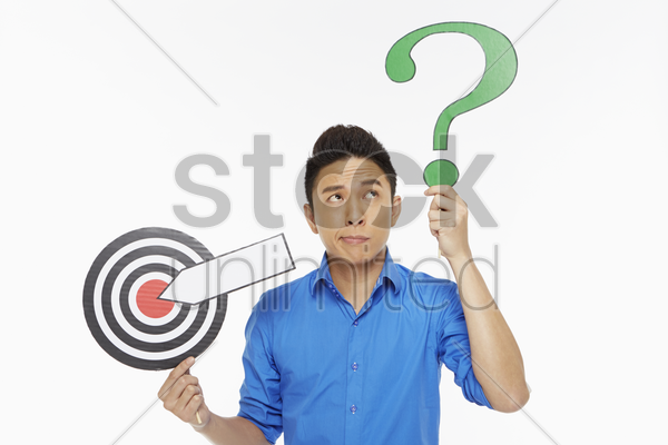 man holding up a dart board along with a question mark symbol stock photo