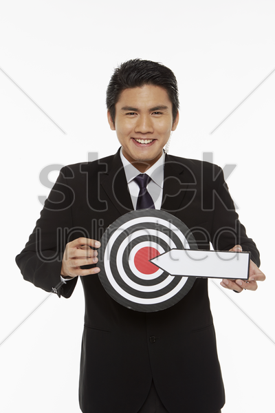 man holding up a dart board stock photo