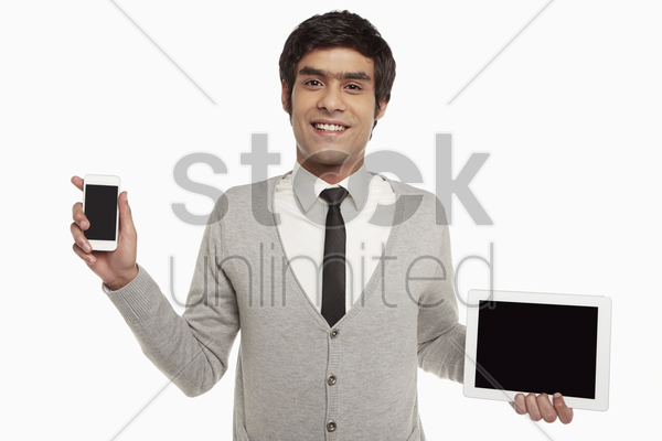man holding up a digital tablet and a mobile phone stock photo