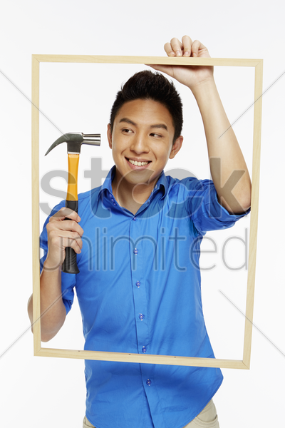 man holding up a hammer and a picture frame stock photo