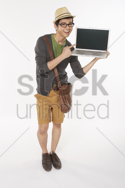 man holding up a laptop stock photo