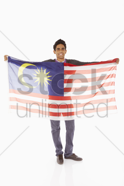 man holding up a malaysian flag stock photo