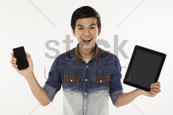 man holding up a mobile phone and digital tablet stock photo