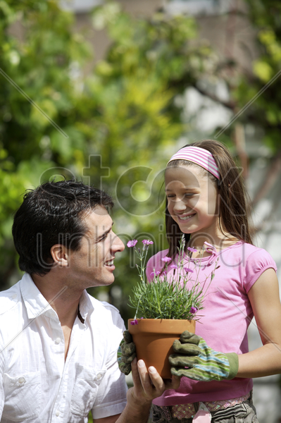 man holding up a pot of flowers to a girl stock photo