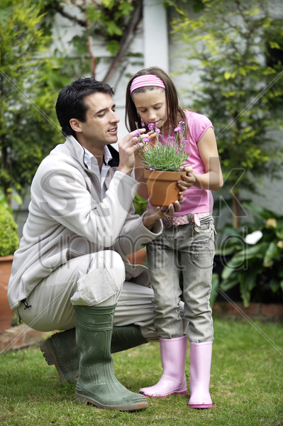 man holding up a pot of flowers with the girl smelling the flowers stock photo