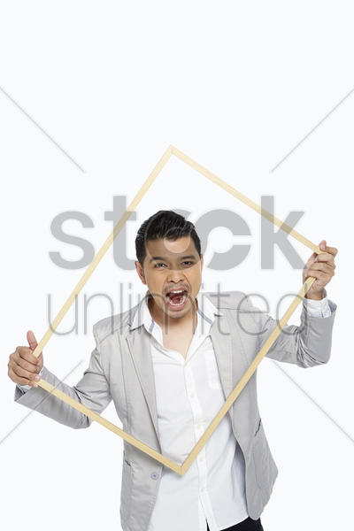man holding up a wooden picture frame, screaming stock photo