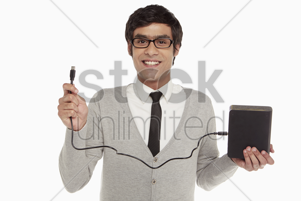 man holding up an external hard disc stock photo
