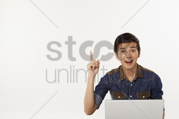 man holding up index finger while using laptop stock photo