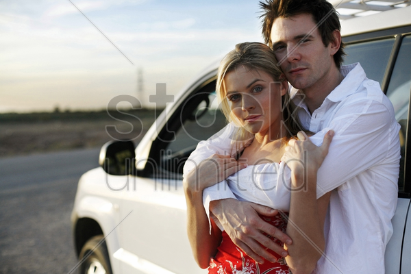 man hugging his girlfriend from behind stock photo