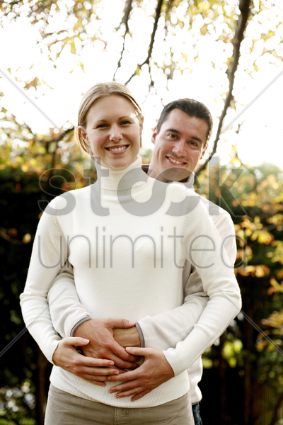 man hugging his girlfriend from the back stock photo