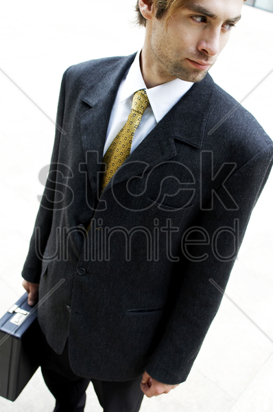 man in business suit carrying a briefcase stock photo
