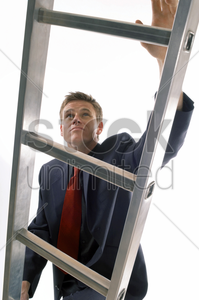 man in business suit climbing up a ladder stock photo