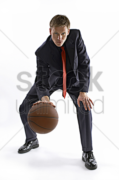 man in business suit dribbling a basketball stock photo