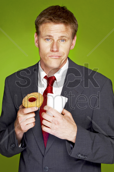 man in business suit holding a cup and a tart stock photo