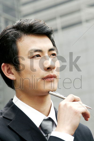 man in business suit holding a pen stock photo