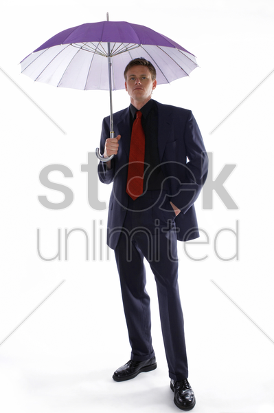 man in business suit holding a purple umbrella stock photo