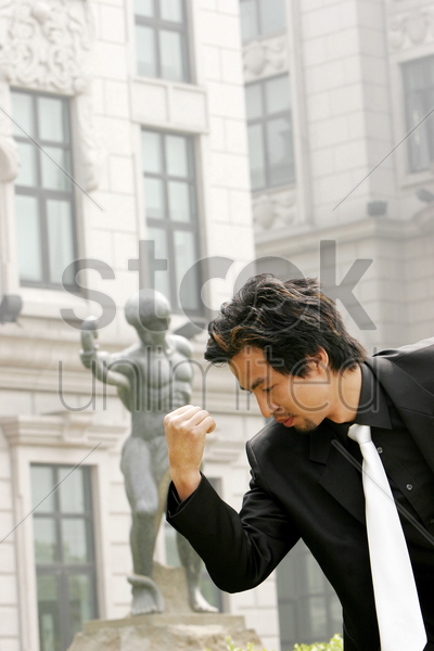 man in business suit imitating a statue's pose stock photo