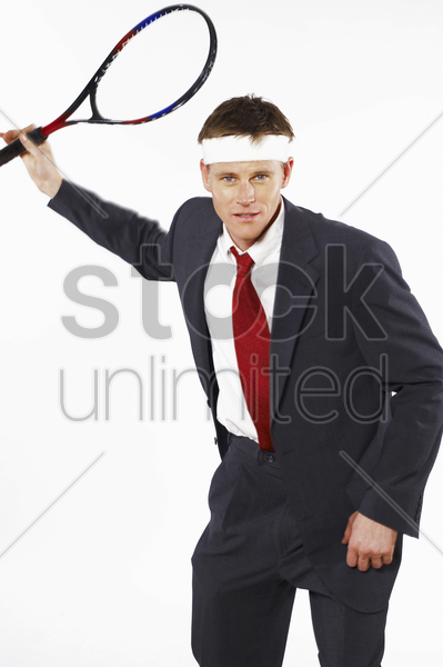 man in business suit playing tennis stock photo