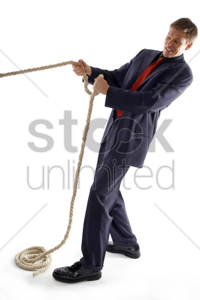 man in business suit pulling a rope with all his might stock photo