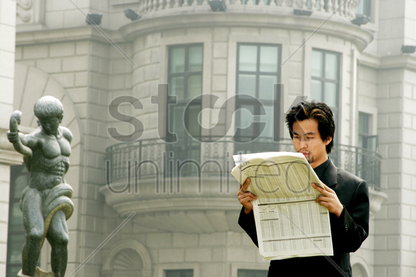 man in business suit reading newspaper stock photo