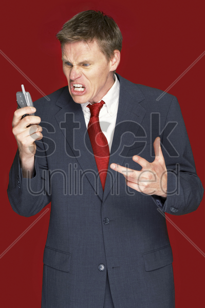 man in business suit shouting angrily on the hand phone stock photo