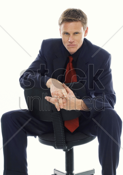 man in business suit sitting on a chair stock photo