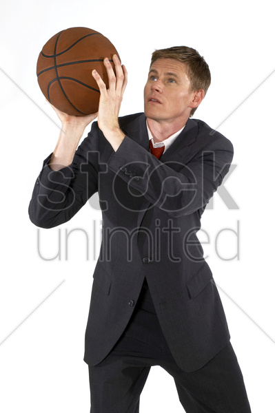 man in business suit trying to shoot a basketball stock photo