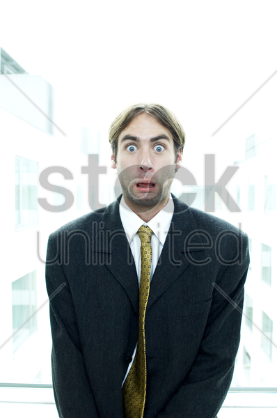 man in business suit with his eyes opened up wide stock photo