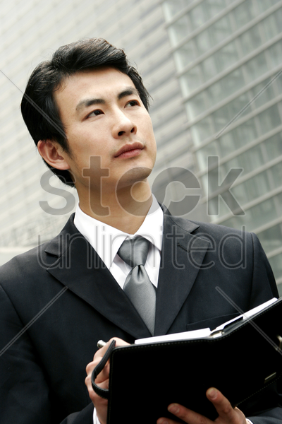 man in business suit writing his organizer stock photo