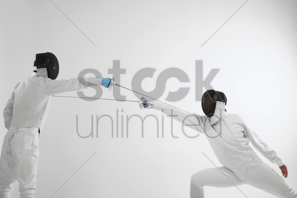 man in fencing suit attacking his opponent stock photo