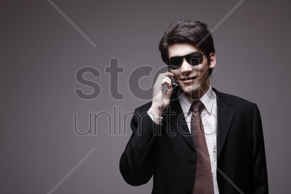 man in full suit with sunglasses talking on the phone stock photo