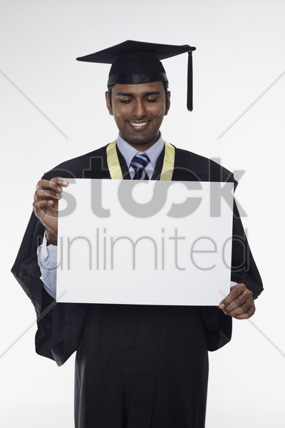 man in graduation robe holding blank placard stock photo