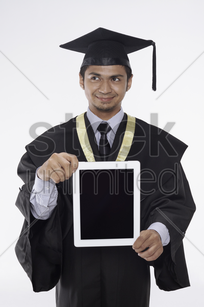 man in graduation robe showing digital tablet stock photo