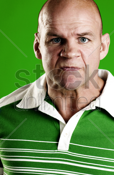 man in green showing his angry face stock photo
