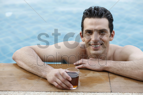 man in pool smiling stock photo