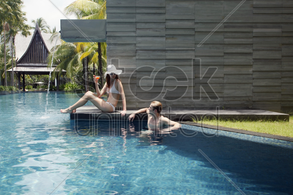 man in pool talking to woman stock photo