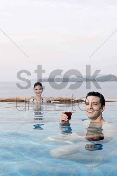 man in pool with a glass of tea, woman relaxing in the background stock photo