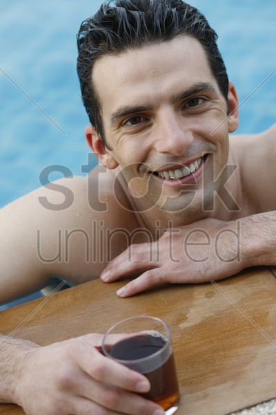man in pool with a glass of tea stock photo