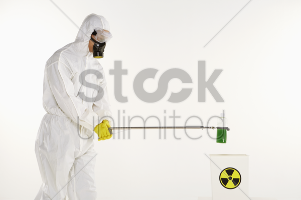 man in protective suit disposing a bottle of chemical stock photo