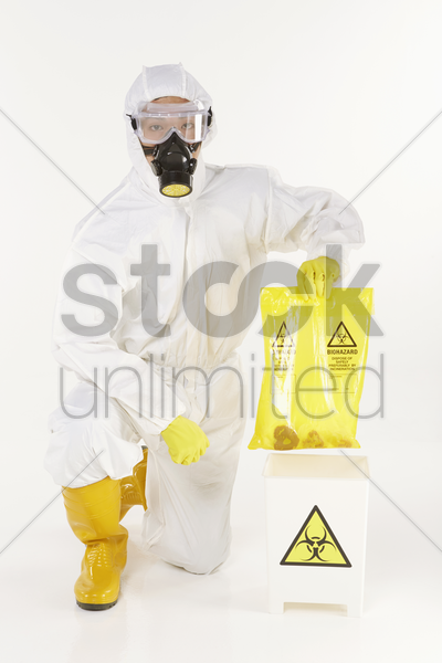 man in protective suit disposing biohazard waste stock photo