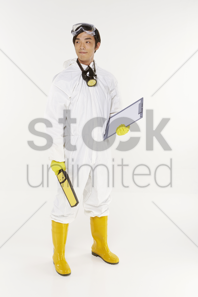 man in protective suit holding a metal detector and clip board stock photo