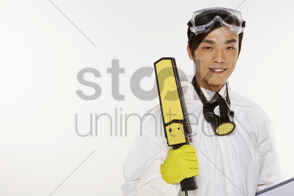 man in protective suit holding a metal detector stock photo