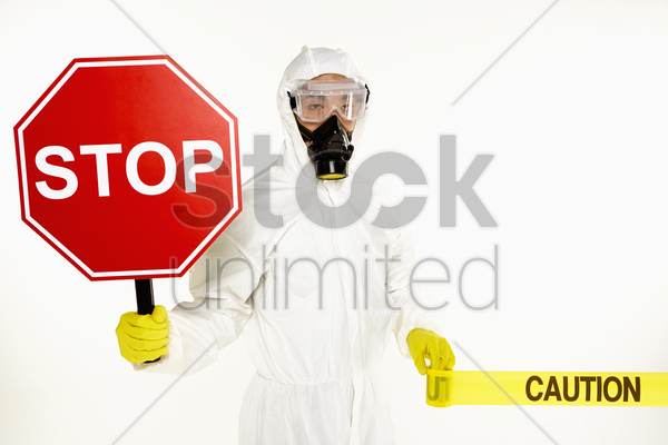man in protective suit holding a 'stop' sign stock photo