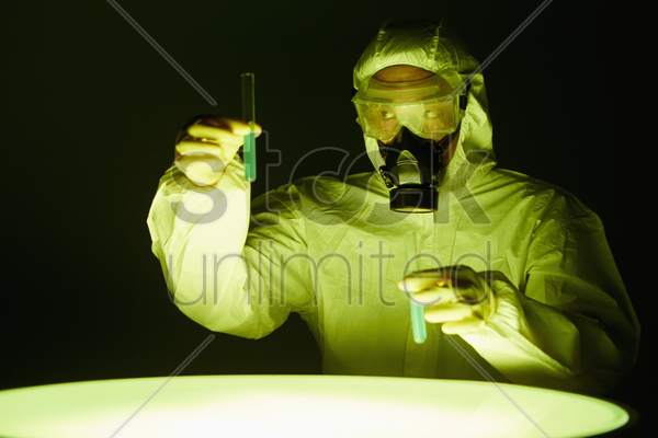 man in protective suit holding test tubes stock photo